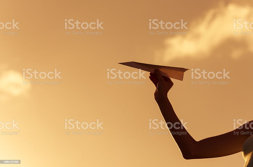 Young female getting ready to throw a paper airplane. stock photo