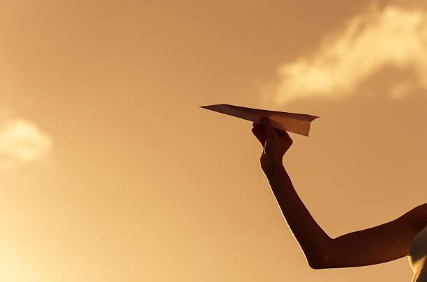 Jovem se preparando para arremessar avião de papel. - foto de acervo