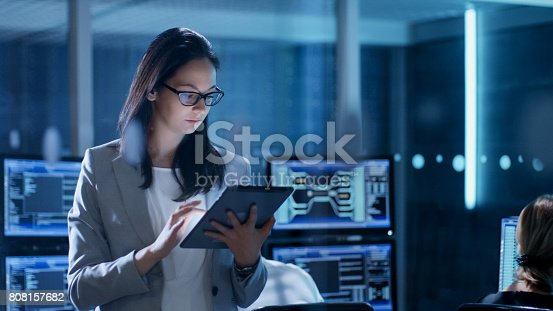Young Female Government Employee Wearing Glasses Uses Tablet in System Control Center. In the Background Her Coworkers are at Their Workspaces with many Displays Showing Valuable Data.