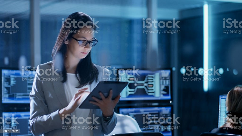 Young Female Government Employee Wearing Glasses Uses Tablet in System Control Center. In the Background Her Coworkers are at Their Workspaces with many Displays Showing Valuable Data. stock photo
