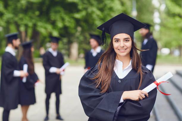 una mujer joven graduada en el contexto de los graduados universitarios. - graduación fotografías e imágenes de stock