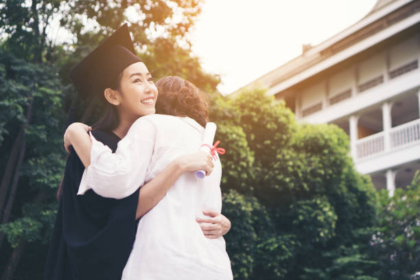 Young female graduate hugging her mother at graduation ceremony, Success,Goal. Education concept. stock photo