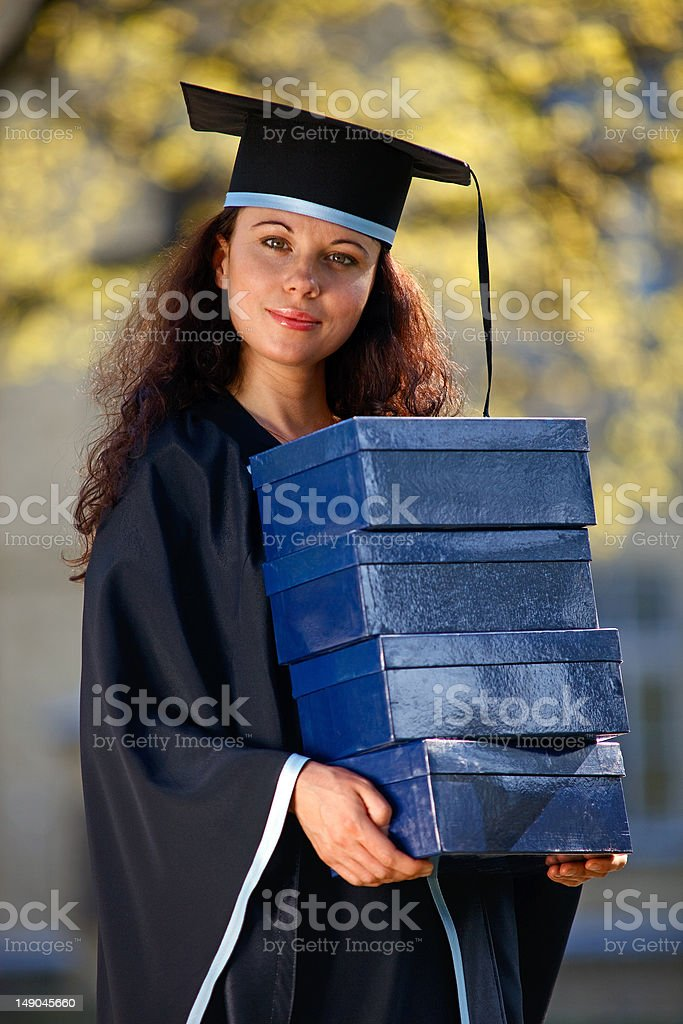 Young female graduate with stack of boxes stock photo