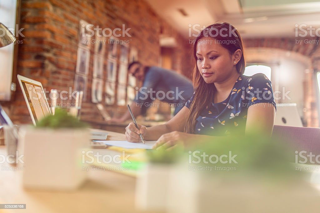 Young female graphic designer working behind a desk stock photo