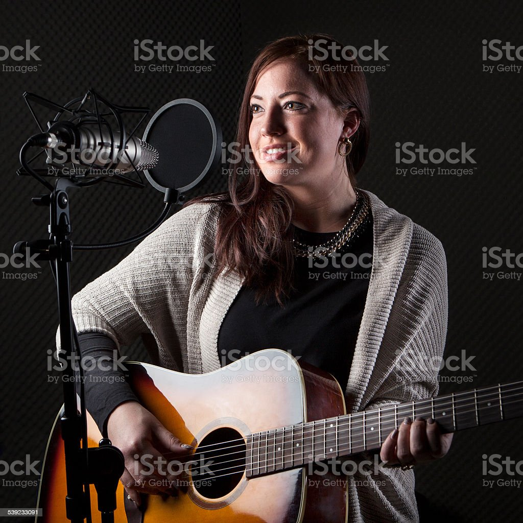 Young female guitar player singer sound recording studio royalty-free stock photo