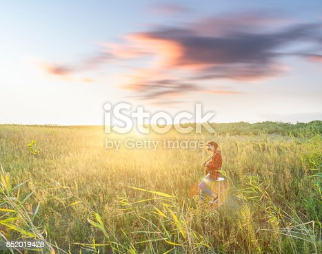 young female guitarist playing guitar in grassy field.
