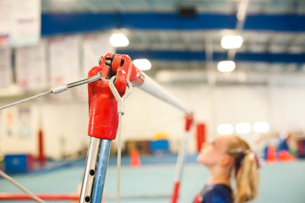 young female gymnast on the uneven bars  - uneven parallel bars stock photos and pictures