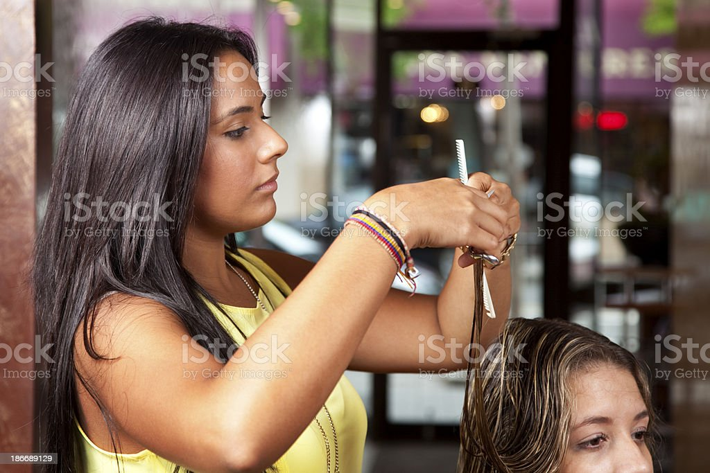 Young  female hair cutter working in salon concentrating on cut royalty-free stock photo