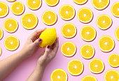 ピンクのパステルの背景にレモンスライスの多くとレモンを保持する若い女性の手