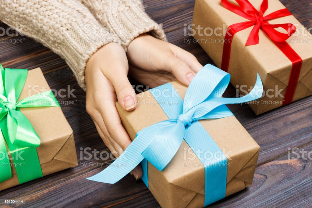 young female hands holding gifts with colorful ribbon stock photo