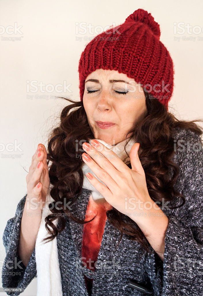 Young female having a cold, sneezing stock photo