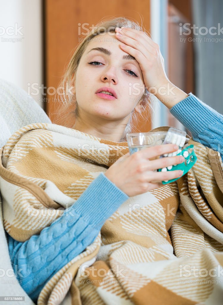 Young female having quinsy and fever and staying in couch stock photo