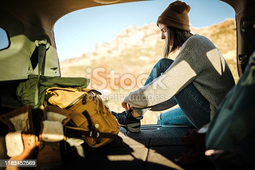 Young woman sitting in car trunk and tying her shoelaces on snickers