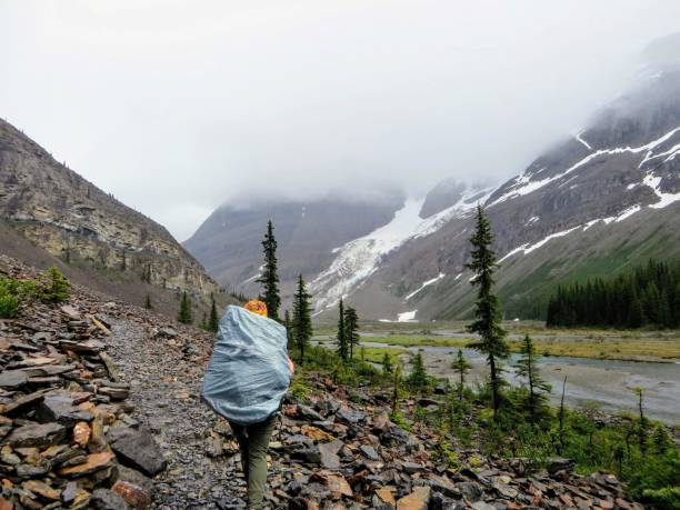 A young female hiker hiking along the Berg Lake Trail, in Mount Robson Provincial Park, British Columbia, Canada.  Mount Robson looms in the distance covered in a thick cloud stock photo