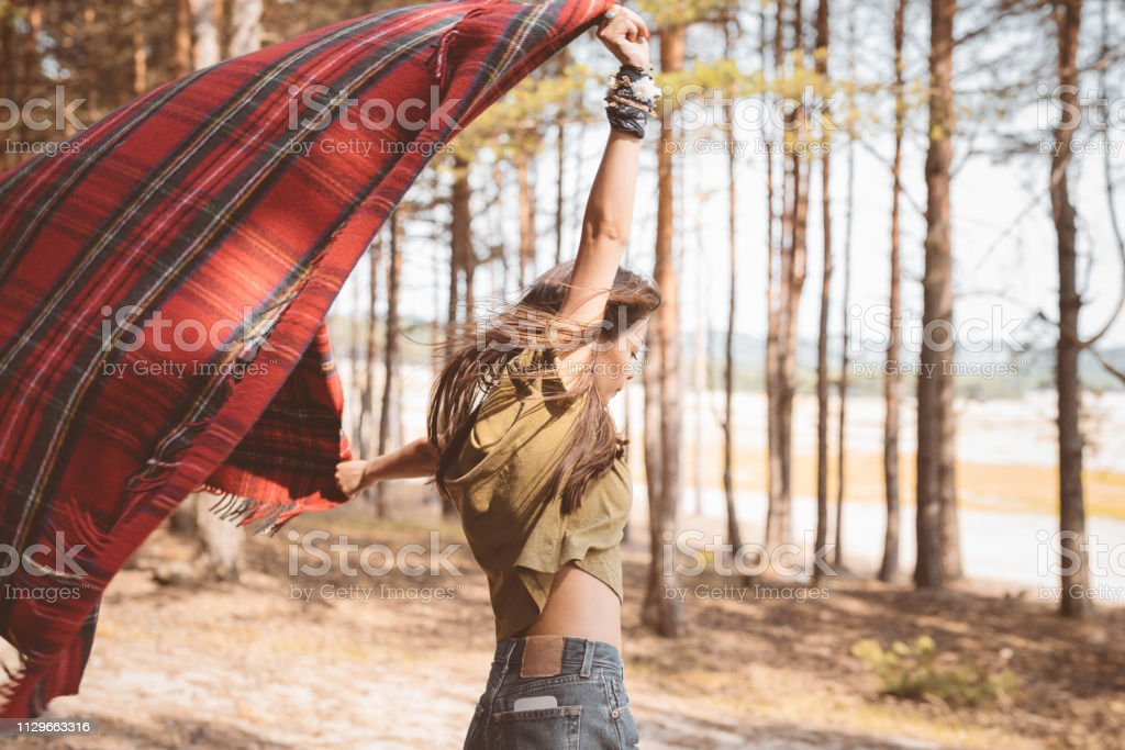 Young female hiker holding blanket in forest Side view of brunette holding blanket with arms raised. Young female hiker is standing in forest. She is enjoying her summer vacation. 25-29 Years Stock Photo