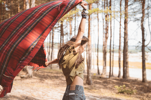 Young Female Hiker Holding Blanket In Forest Stock Photo - Download Image Now