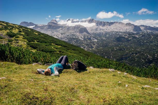 Junge weibliche Wanderer auf grasbewachsenen Hang liegend – Foto