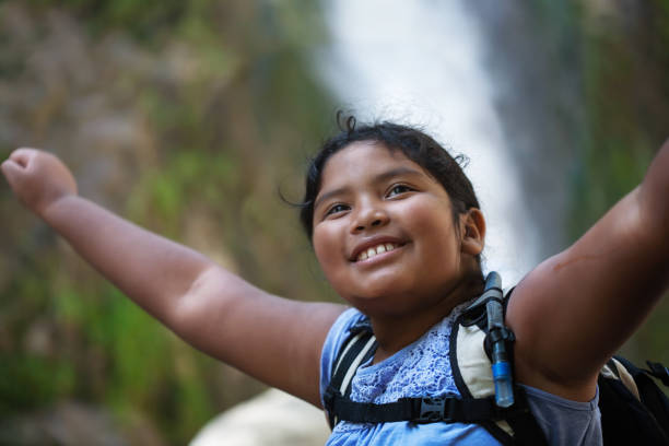A young female hiker raising her arms into the air, accomplishment of a difficult hiking trail, with waterfall in the background. stock photo