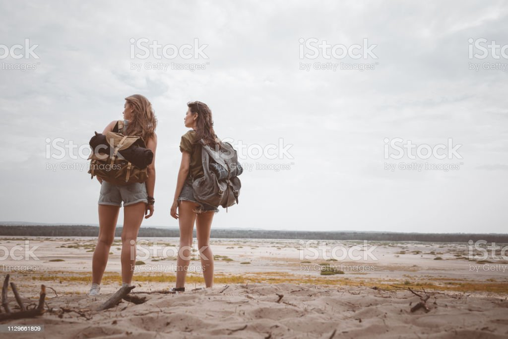 Young female hikers looking at desert landscape Full length of female hikers looking at landscape. Rear view of young women are standing with backpacks. They are spending summer vacation together. 20-24 Years Stock Photo