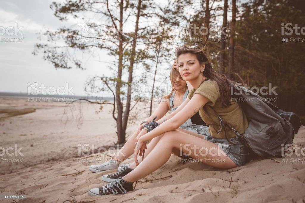 Young female hikers sitting on sand in desert Portrait of beautiful woman sitting with friend in desert. Full length of young female hikers are spending summer vacation. They are with backpacks. 20-24 Years Stock Photo