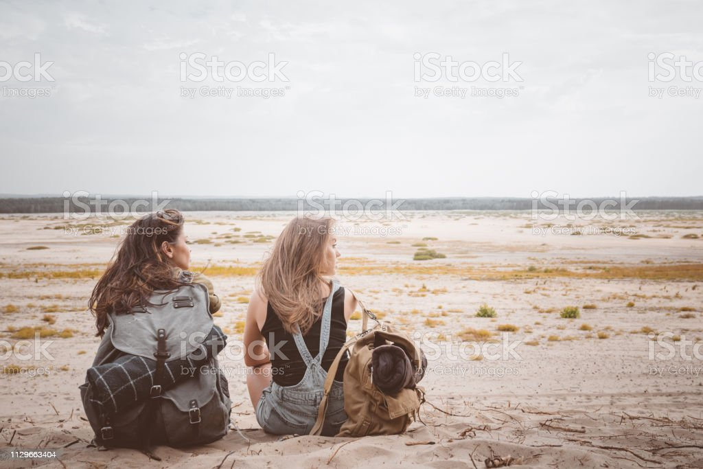 Young female hikers sitting with backpacks on sand Rear view of female hikers sitting with backpacks on sand. Young women are looking at landscape during summer vacation. They are in desert. 20-24 Years Stock Photo