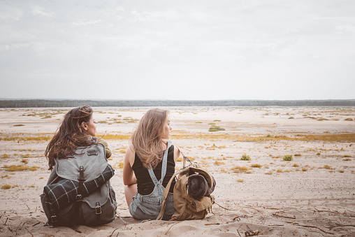 Young Female Hikers Sitting With Backpacks On Sand Stock Photo - Download Image Now