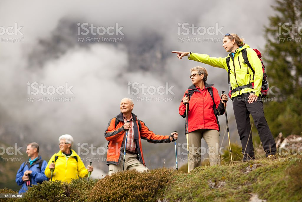 young female hiking guide showing senior group surrounding mount stock photo