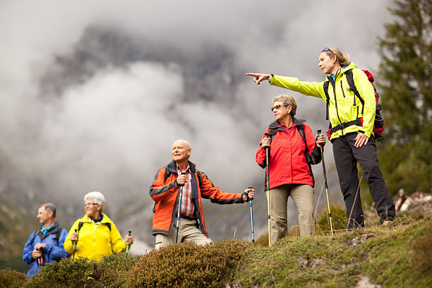 young female hiking guide showing senior group surrounding mount - guide stockfoto's en -beelden