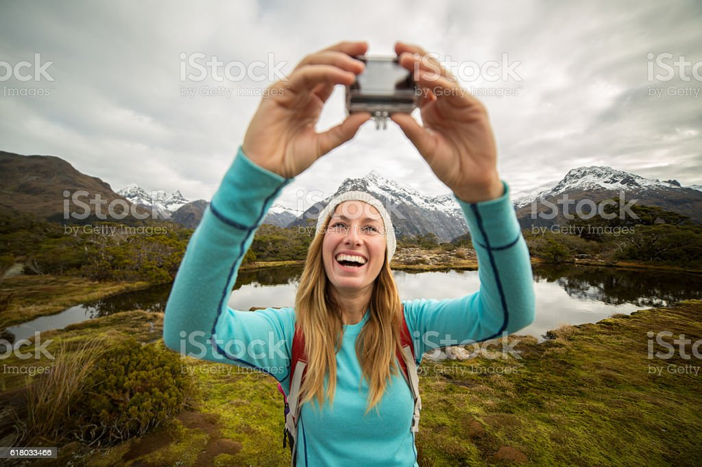 Young female hiking takes selfie portrait using wearable camera – Foto