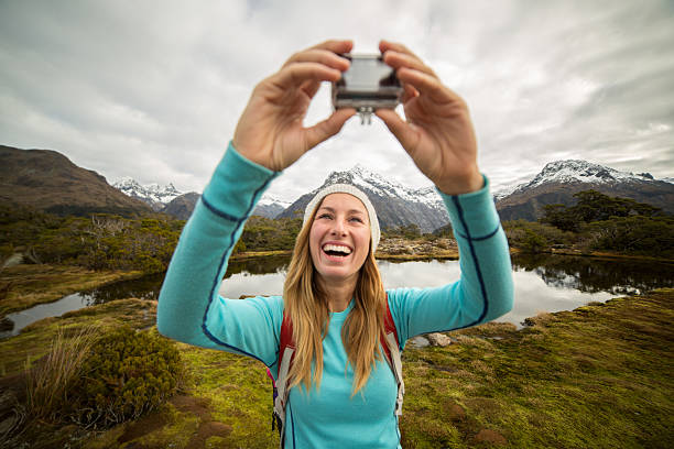 young female hiking takes selfie portrait using wearable camera - gopro stockfoto's en -beelden