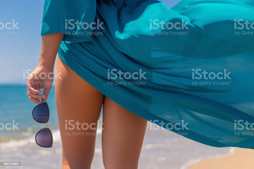 Back view of young female holding glasses on the beach close up