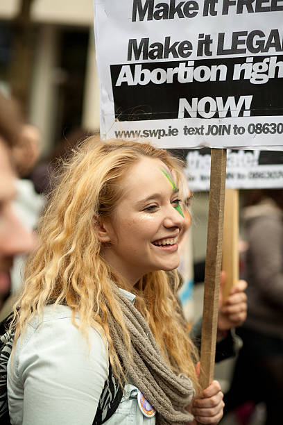 young female holding poster of Socialist Workers Party Dublin, Ireland - September 29, 2012: Dublin March for Choice 2012, young female holding poster of Socialist Workers Party   pro choice stock pictures, royalty-free photos & images