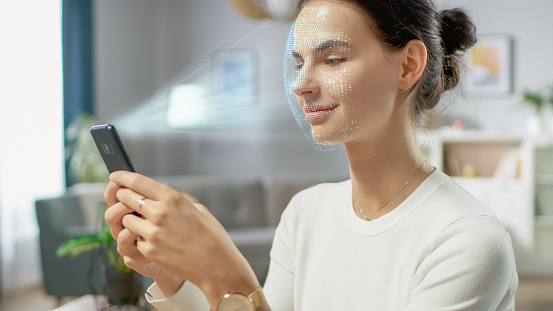 istock Young Female Identified by Biometric Facial Recognition Scanning Process from Her Smartphone. Futuristic Concept: Projector Identifies Individual by Illuminating Face by Dots and Scanning with Laser 1159763168