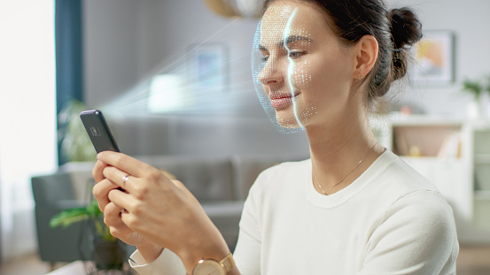 istock Young Female Identified by Biometric Facial Recognition Scanning Process from Her Smartphone. Futuristic Concept: Projector Identifies Individual by Illuminating Face by Dots and Scanning with Laser 1159763169