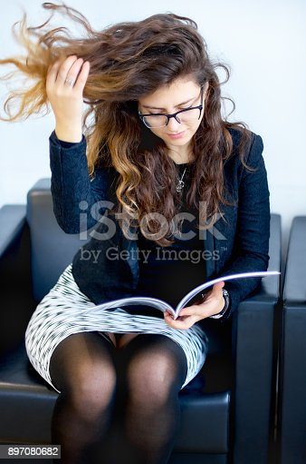istock Young female in a business suit is sitting in a chair, leafing through a magazine 897080682