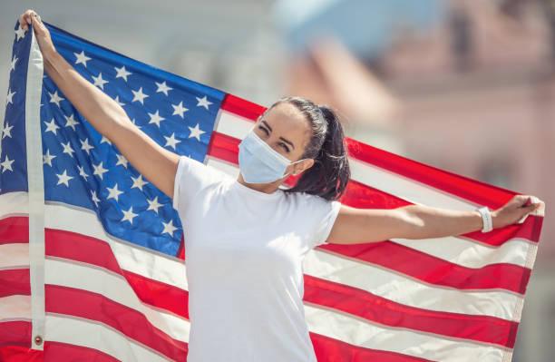 Junge Frau in einer Gesichtsmaske, die eine US-Flagge hinter ihrem Rücken im Freien hält. – Foto
