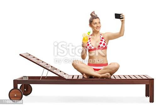 Young female in bikini drinking a cocktail and taking a selfie with a selfie stick isolated on white background