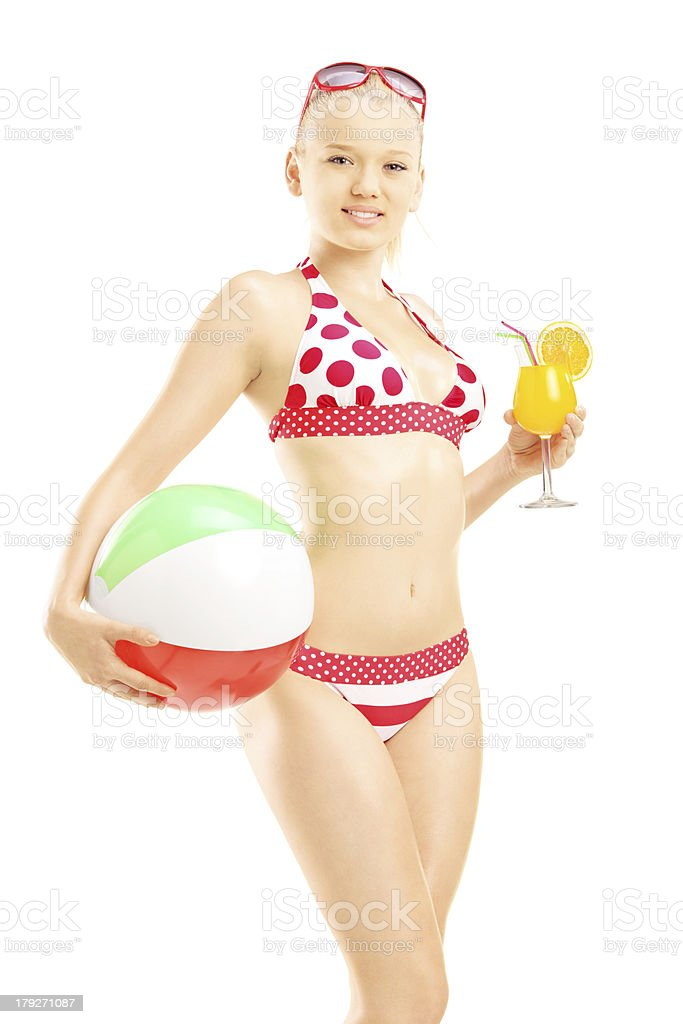 Young female in bikini holding a beach ball and cocktail royalty-free stock photo