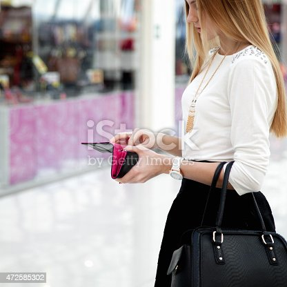 istock Young female in fashionable clothes looking into a wallet 472585302