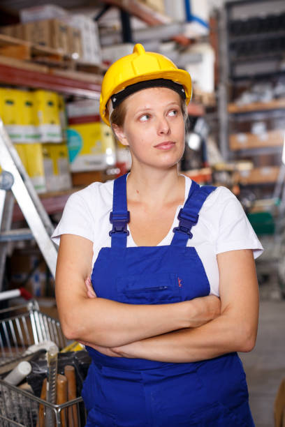 Young female in uniform and helmet standing near basket with construction  materials stock photo