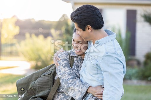 Young, Hispanic, smiling female in uniform hugs a young, mid-adult male excitedly. They both stand outdoors in front of a home.