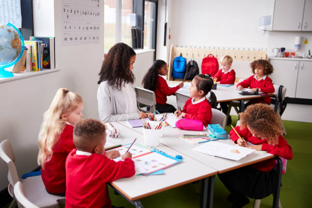 Young female infant school teacher sitting at a table in a classroom with her pupils stock photo
