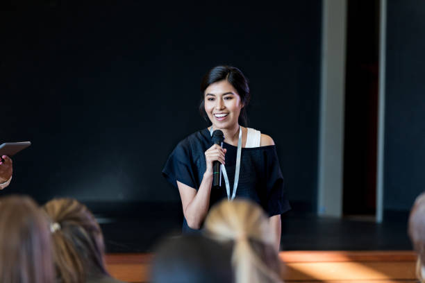 Young female influencer speaks with crowd during seminar Young Hispanic woman gives a motivating speech during a conference or seminar. speech stock pictures, royalty-free photos & images