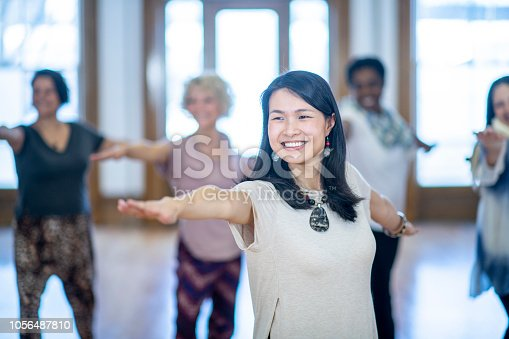 A young asian female yoga instructor smiles as she teaches her class a pose. Her hands are stretched out and her friends are doing the same.
