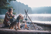 Young woman is sitting and drinking tea next to the campfire with her dog next to her