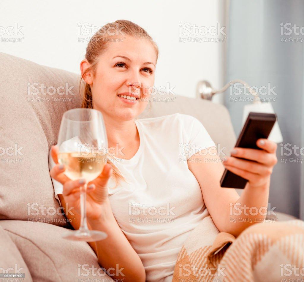 年輕的女性正在看電視, 坐在白葡萄酒 - 免版稅享受圖庫照片