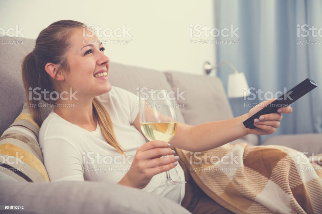 Young female is watching TV and sitting with white wine royalty-free stock photo