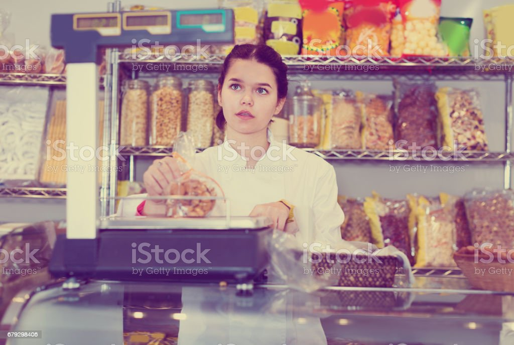 Young female is weighing cookies royalty-free stock photo