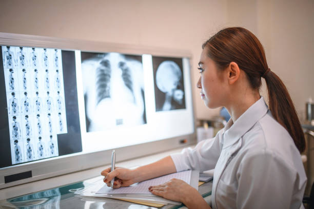 若い女性看護師がx線を研究し、メモを取る - people of color ストックフォトと画像
