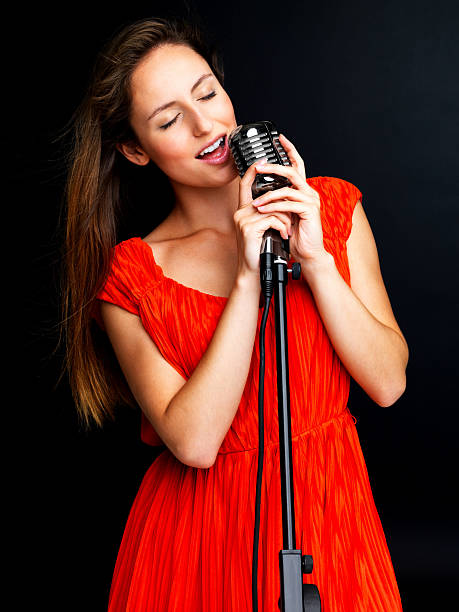Singer Standing In Front Of A Microphone And Singing Stock